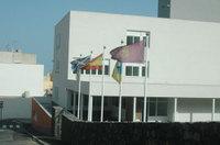 Una empresa constructora coloca su bandera en la entrada de un colegio público